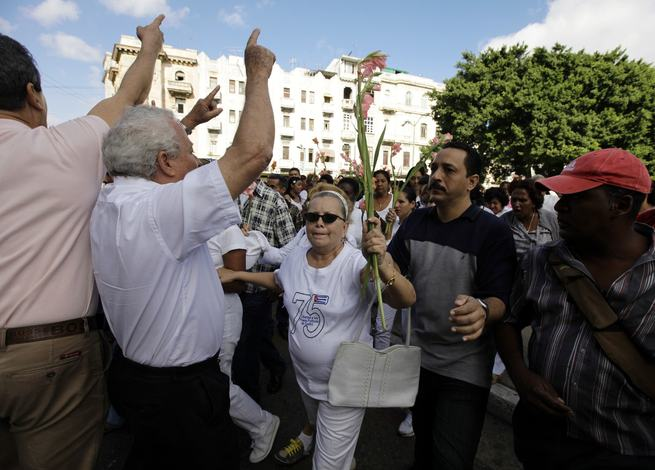 Pollan, leader of Ladies in White, marches as government supporters shout slogans around her in Havana
