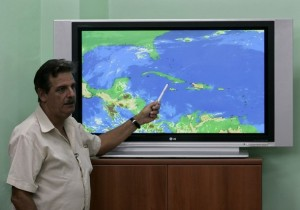 Jose Rubiera, Cuba's chief weather forecaster, talks to Reuters while standing next to a satellite image  at the Cuban National Weather Institute in Havana